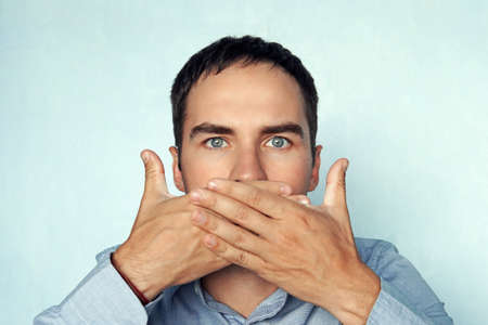 man covers her mouth. businessman closes his mouth. Фото со стока