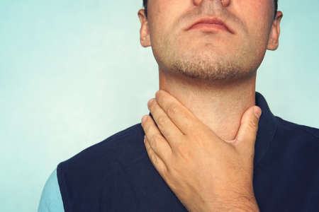 Young man having sore throat and touching his neck, wearing a loose t-shirt against light blue background. Hard to swallow. nodule in the thyroid gland 스톡 콘텐츠