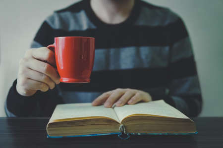man reading book with coffee or tea. Red Cup in hand. A man in a striped sweater.