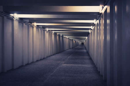 tunnel, underground pedestrian crossing at night. A long concrete tunnel with lanterns in the city underground. Underpass.
