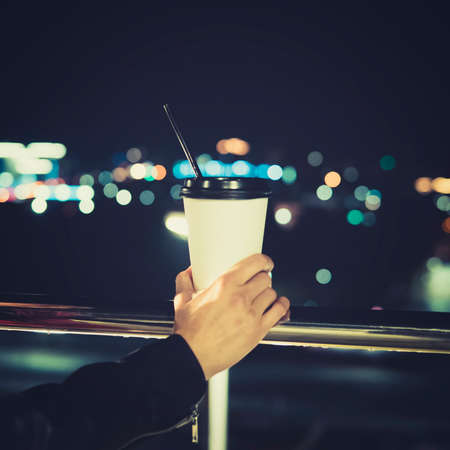 Holding a cup of coffee and raise my hand to take a picture with a blurry background. A white cup of coffee without logo that can use for your logo. atmosphere of night life. Stock fotó