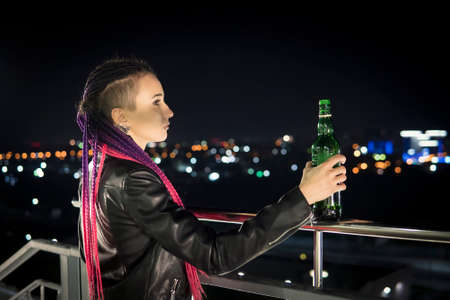 Portrait of lonely woman drinking alcohol from bottle at highway. A young drunk girl with a bottle of whiskey stands on the roof of the house and looks down at the night city.