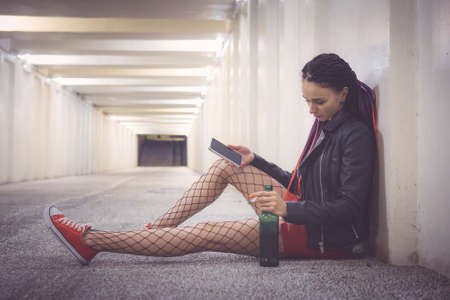 Girl in black jacket red dress and mesh pantyhose sitting on the pavement in underpass and drinking alcohol looking at the phone with sadness on his face. Broken relationships. Emotional experience.