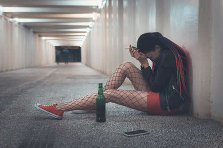 girl is experiencing grief and drinking alcohol. woman feel depression and alcoholism. Young drunk girl sitting with a bottle of whiskey in the underpass or tunnels. unrequited love. loneliness