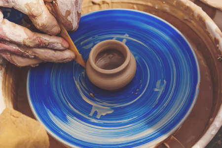 The man - Potter from the clay pitcher on a Potter's wheel. The old craft of pottery making