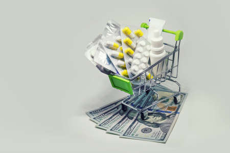Shopping cart full of drug and medicine pills on dollar money, pharmaceutical cost concept. medications in the cart. buying medicines