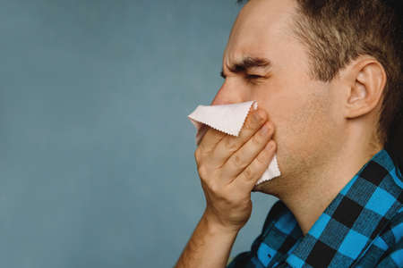 Allergic reaction. the guy blows his nose and sneezing. The guy wipes his nose with a handkerchief after sneezing. Seasonal allergies.