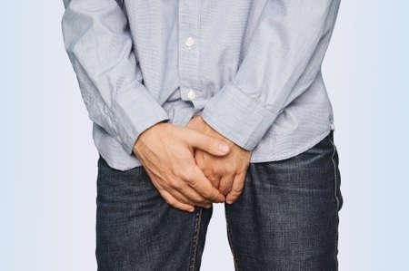 L'uomo graffia il prurito con la mano, il pene, il prurito, il concetto con l'assistenza sanitaria e la medicina. L'uomo è in piedi con le braccia incrociate all'altezza dell'inguine