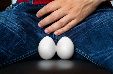 a man holds the crotch. chicken eggs as a symbol of male theskill. Health problems in men erased age