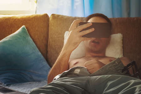 Young naked man watching pornography. young man jerks off on the couch watching the screen of a smartphone