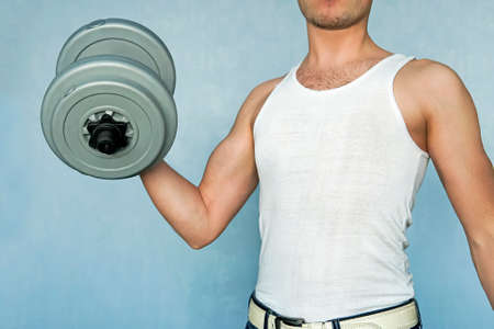 an aspiring athlete trains your biceps. beginning sportsman. guy raising a dumbbell. Home exercises for weight gain. Standard-Bild