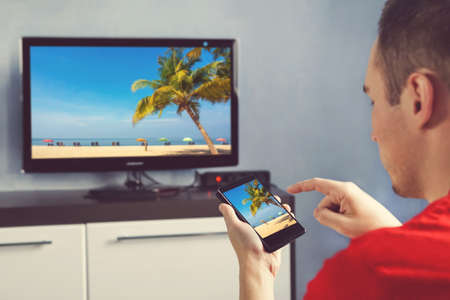 Mature Man With Smartphone Connected To A TV Watching Movie At Home. relaxed man with smartphone connected to a tv and envisioning photos in networking