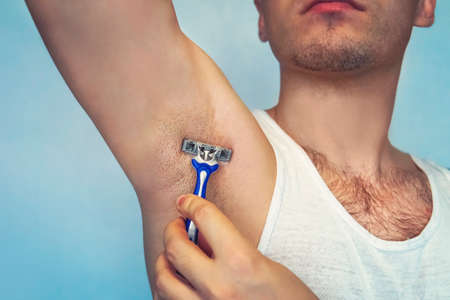 underarm hair removal. Male depilation. Young attractive muscular man using razor to remove hair from his body. the self-care concept. epilation Stock Photo