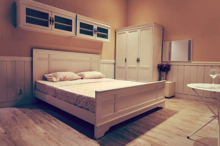 White wooden bed with white linens. Stylish interior design in bright colours. Expensive room in a five star hotel.