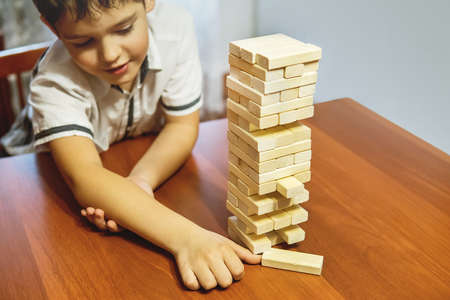 Boy playing wood tower game on wooden table