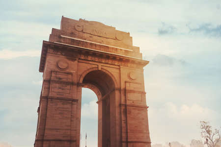 Historic India Gate Delhi - A war memorial on Rajpath road New Delhi. main Indian historical landmark in the background of the cloudy sky in the sunlight Фото со стока
