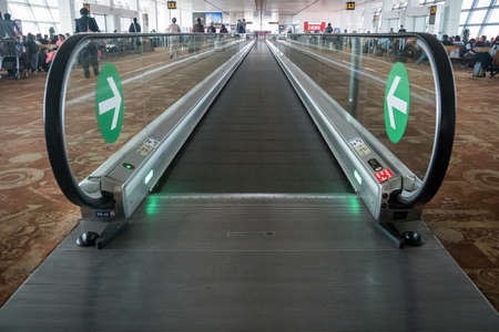 Movable conveyor belts at the airport, straight flat escalator.