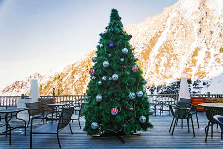 Beautiful Christmas tree decorated with balls and garlands on the background of the mountains in an outdoor cafe in the daylight high in the mountains.