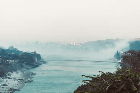 Morning in the mountains. The Ganges River in the foothills of the Himalayas. India. view of Lakshman Jhula bridge early morning. smoke on the water
