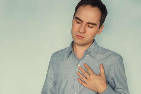 Hombre joven en camiseta blanca con fuerte ataque al corazón, dolor mental, sufrimiento mental. experiencia, sentimiento, emoción, preocupación, Foto de archivo