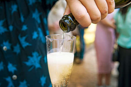 A close up of a half-filled goblet of champagne held by a man at the outdoor festive event. The male wedding guest fills the glass with sparkling wine at the blurred background. Wedding traditions Imagens