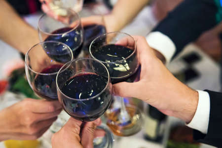 Male and female hands with filled glasses of red wine above the restaurant tabletop. Drinking toasts and clinking tumblers at a formal dinner party. Drinking wine at banquet. In full swing of feast.