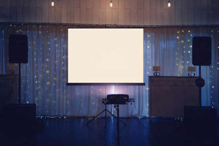 Illuminated banquette hall stage with a big white screen and acoustic systems. Equipment for video and audio projection at a festive event. Banquette stage with a board for projection in the centre.