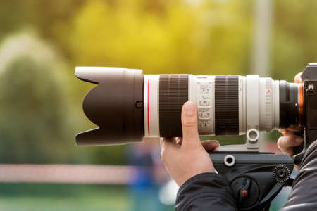 Handshot of a professional photographer outdoors. Man holds a modern camera device. Cameraman shoots outdoors. Shooting with lens. Paparazzi with high-end optical objective. Photographic equipment.