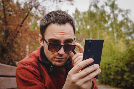 cute attractive handsome serious guy wearing casual clothes and sunglasses outside holding smartphone reading sms. Work through smartphone. Correspondence in social network. Student in Park chatting