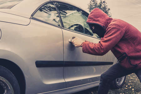 Side view of car being forced by a man in hoodie and mask. Thief tries to steal vehicle from a parking. Young male acts alone breaking the car door. Unknown person picklocks the automobile. Car fraud. 版權商用圖片