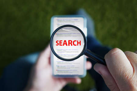 Close up of a man sitting and looking through magnifying glass with red written word Search on the lens to the smartphone screen. Using mobile internet in searching information. Browsing in cellphone. Banco de Imagens
