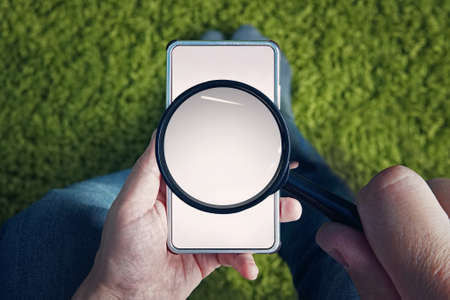 Top-down view to sitting man with blank smartphone and magnifying glass above its screen. Man holds magnifier to find something in mobile internet. Use of cell phone for searching information online.