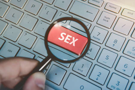 Man holds magnifying glass above the enter red key with the written word Sex on the computer keyboard background. Searching for sex dating in internet. Virtual dating services. Watching porn online
