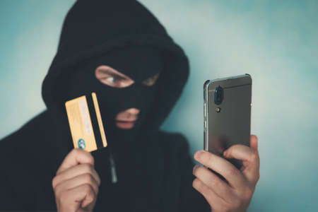 Close up of a man in robbery mask and hood holding the credit card and looking at the smartphone screen. Male criminal arranges a financial affair with mobile and credit card. Network fraud dangers.