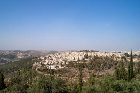 Panoramic aerial view on highway among the hills of Jerusalem, Israel. Modern houses of Jerusalem on a slope on the outskirts of the city among the trees. Foto de archivo - 128293374