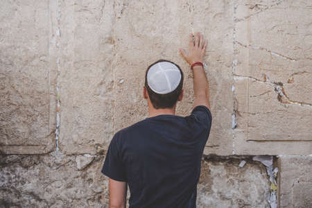 Man hand and pray paper on the Western Wall, Wailing Wall the Place of Weeping is an ancient limestone wall in the Old City of Jerusalem. Second Jewish Temple by Herod the Great