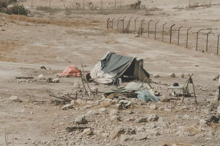 Bedouin houses in the desert near Dead Sea. Poor regions of the world. A indigent Bedouin sitting at the tent. Poverty in Jordan. middle East