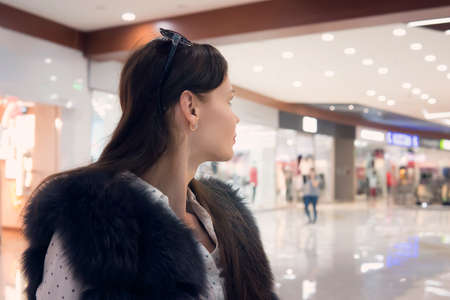 Close up of a young brunet girl in shopping mall looking away from the camera. Good-looking woman stands in shopping centre walk and looks into the distance