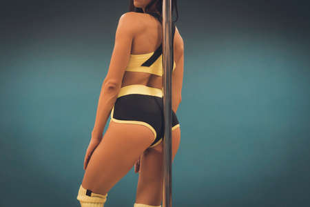 Close up of athletic sexy body of pole dancer leaning with her back against pylon. Stripper in pole dance yellow and black outfit at dark blue background. Hot figure of pole professional with pylon.