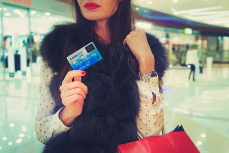 Half-face shot of young chic woman with red lips in shopping centre holding credit card and bag in hands. Trendy brunette girl is going to do shopping using payment card. Lady in fur jacket in store