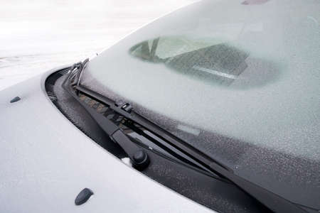 Windscreen wipers cleaning a windshield of a car from the snow. defrost, defroster in the cold