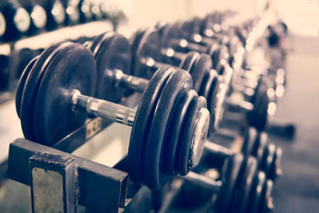 Rows of dumbbells in the gym with hign contrast and monochrome color tone. concept of bodybuilding. Imagens