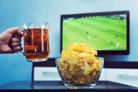 Beer potato chips and Sport on TV. A man raises a mug of dark beer celebrate the victory of his favorite team