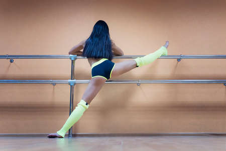 Athletic woman standing near barre in fitness center putting her leg high on the choreographic machine. Brunette dancer in sport outfit warming up before dancing. Stretching in dance class. Work out