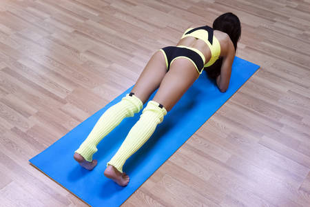 High angle view of beautiful healthy sporty enduring graceful strong muscular girl doing core exercise in gym. Female body builder in plank pose on elbows on mat. Woman on floor practicing plank.