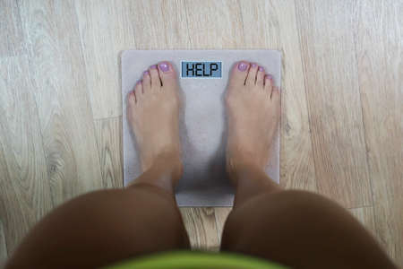 Top-down view to female bare feet standing on scale with written word Help on display. Concept of fitness and loosing weight. Woman needs to become slimmer. Scale showing dieting and shaping time.