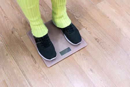 Feet of fitness woman wearing legwarmers and trainers standing on scales. View to female legs in sneakers standing on scales for checking weight after exercising. Losing weight after working out