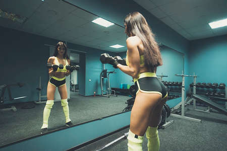 Female fitness coach with long dark hair in top and tiny sport shorts posing with dumbbells against the mirror of empty gym room. Sporty woman lifting weight in fitness club reflecting in mirror.