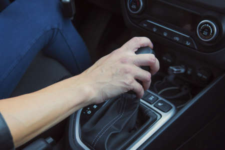 Close up of woman shifting gears on automatic gearbox and driving car. Female hand shifts the hydro sitting in a vehicle. Auto business, car sale, consumerism, transportation and travelling concept. 스톡 콘텐츠