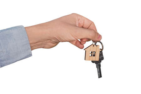 A mans hand isolated on a white background dropping a set of keys. real estate transaction. A mans hand holds the key to the apartment with a keychain in the form of a house. a realtor sells a house. 写真素材